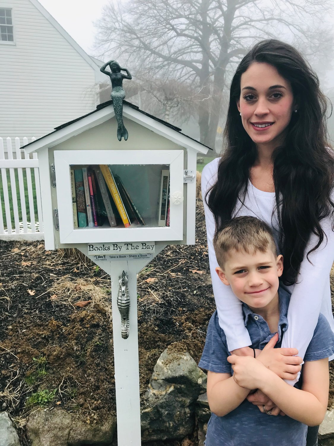 "Cassandra Levy with her son, Bryce, at the ""little free library"" she installed in her neighborhood in Center Moriches."