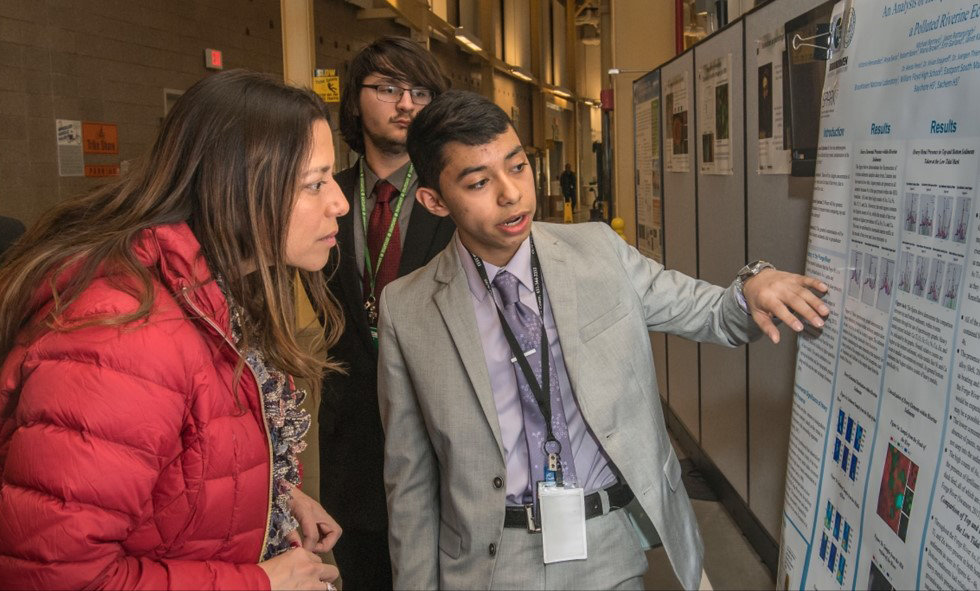 Michael Borrayo and Kyle La Spisa are pictured explaining their research to NYS Senator Monica Martinez.