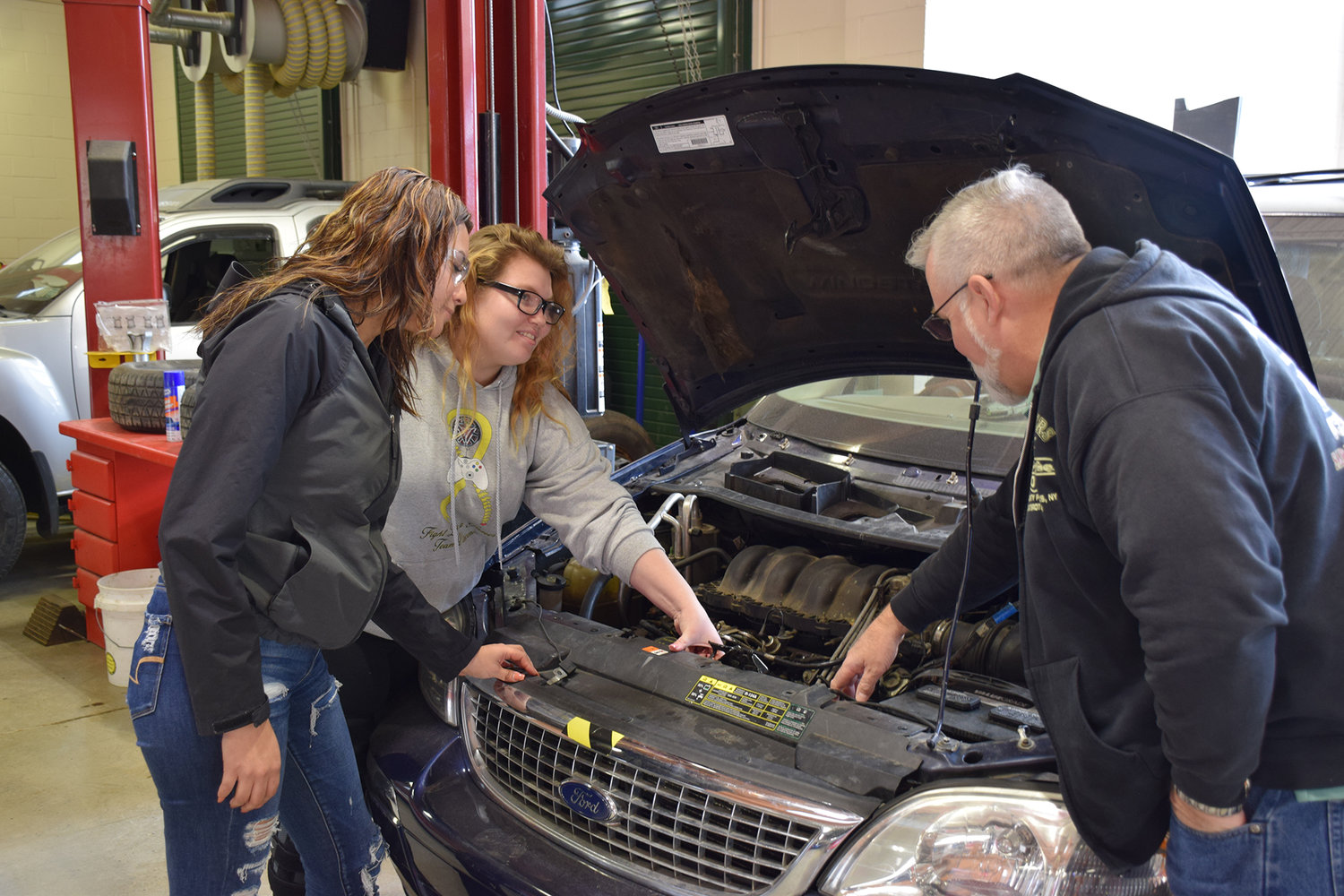 Senior Morgan Molinary (center) and junior Joselyn Noriega (left) are first- and second-year automotive students, respectively, at William Floyd High School — two of five in the program since its inception about seven years ago.