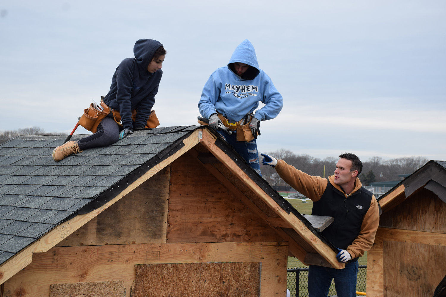 Yep, there are girls on the roof: Juniors Giovanna Capitello (left) and Lauren Chavez (center), carpentry students at William Floyd High School, install the roof on their shed project with the help of teacher Mathew Van Horne (right).