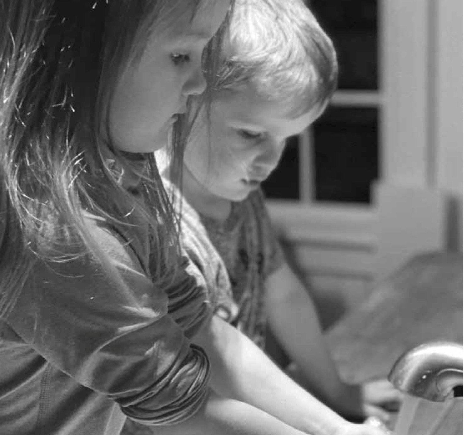 Big sister Makena Berube, aged 4, from Bayport, helps her younger brother Jack, age 3, learn the intricacies of hand-washing.