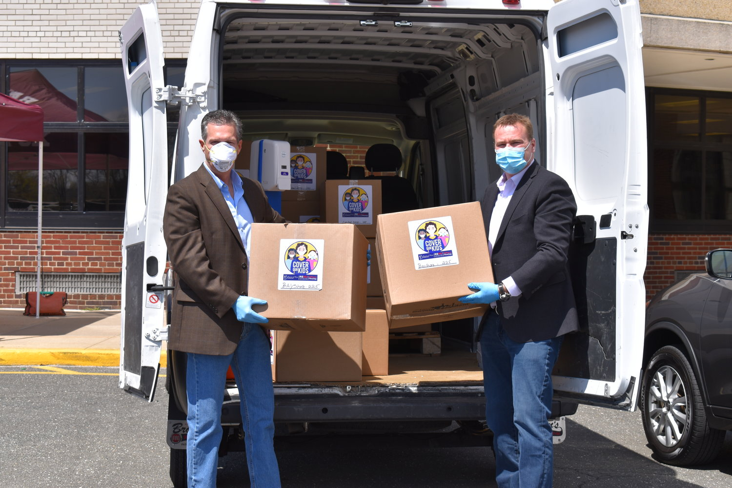 Bay Shore Schools superintendent Joseph Bond and Michael VanDenburg, principal of RENU Contracting Restoration and Milburn Flooring, unload the mass donation of non-surgical masks for students to pick up in addition to grab-and-go meals during the COVID-19 pandemic.
