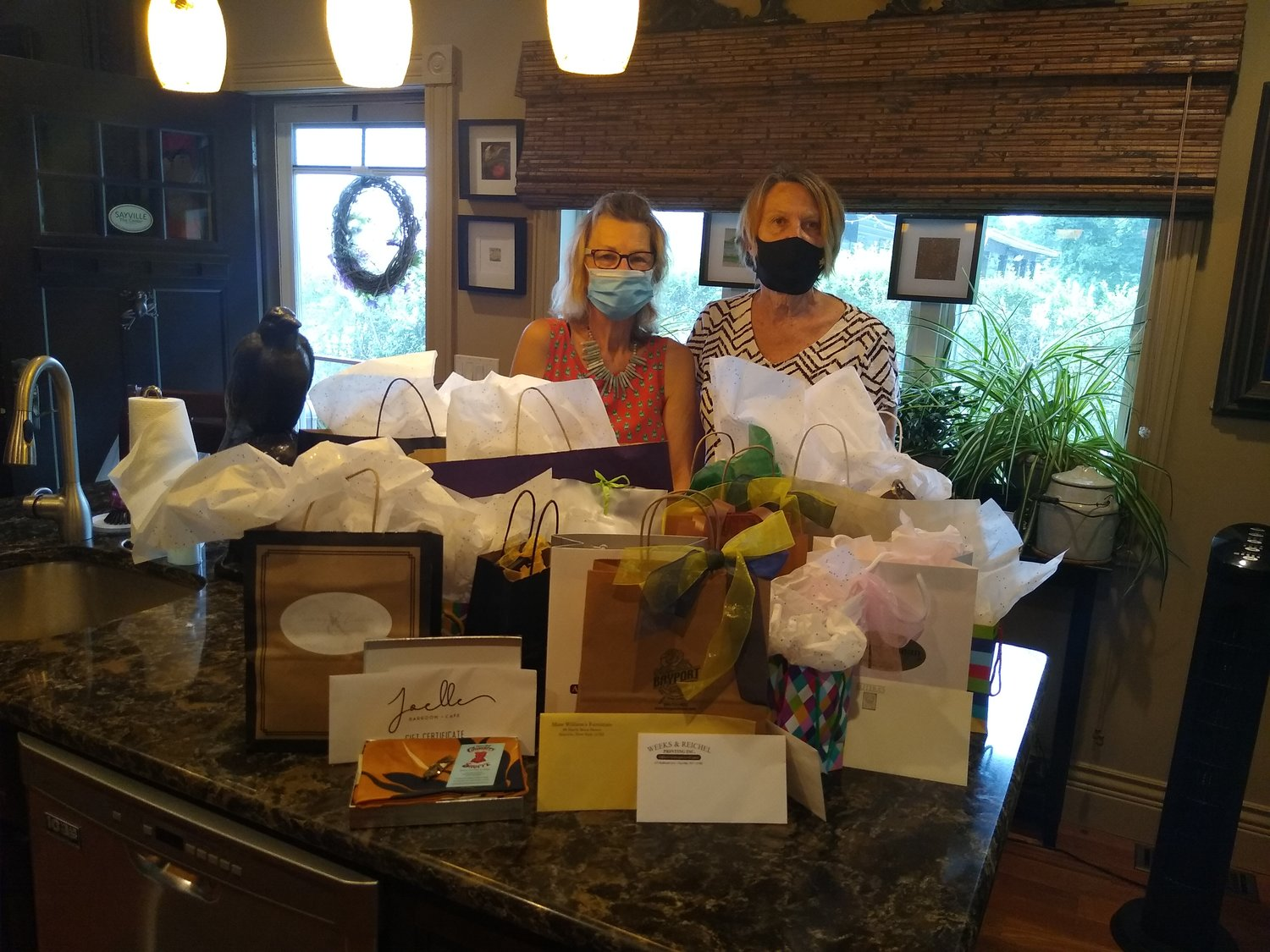 President Barbara Fitzpatrick (left) and first vice president Bernice Corbin (right) of the Sayville Village Improvement Society are pictured with over $1,000 worth of purchases made by the SVIS at local vendors for their future fundraisers.