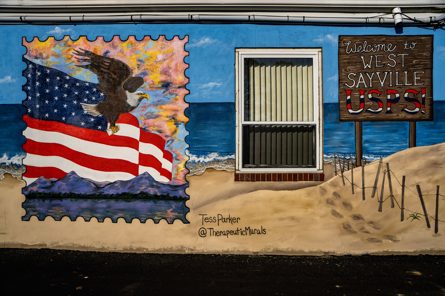 Echoing the original mural, artist Tess Parker included a postage stamp as part of her vision with an all-American theme featuring an eagle carrying a letter, a waving flag, and purple mountains on the south side of the West Sayville post office building.