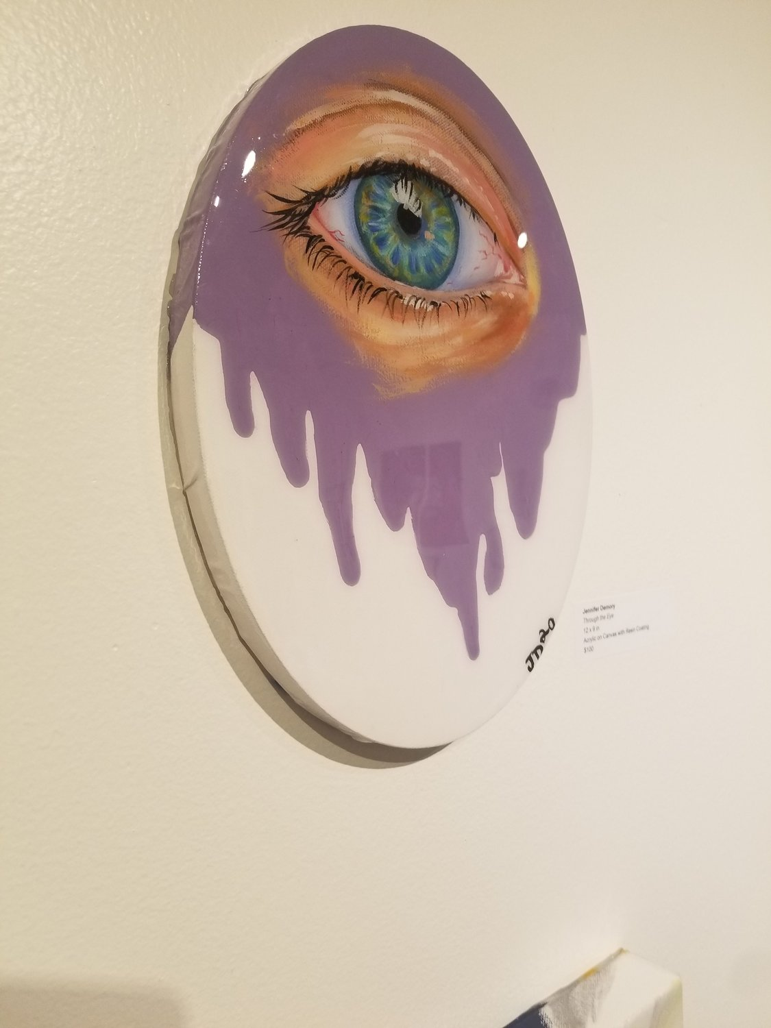 """Through the Eye"" by Jennifer Demory. 12x9 inches. Acrylic on canvas with resin coating. $100. The hyperrealism of the fantastic blue eye is contrasted with an almost '80s homage to unicorn purple spilling through. Encased in resin, Demory  creates a freak show of preservation of the all-seeing eye."