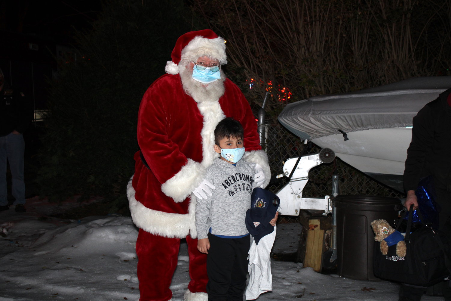 Six-year-old Joshua, of Shirley, receives his Make-A-Wish gift from Santa Claus outside his home on Beachwood Drive on Dec. 23.