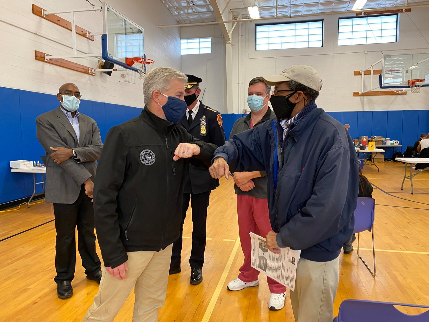 Suffolk County executive Steve Bellone greets an individual who received the first dose of the vaccine at Boys & Girls Club of Bellport for the MLK Day of Service on Jan 18.
