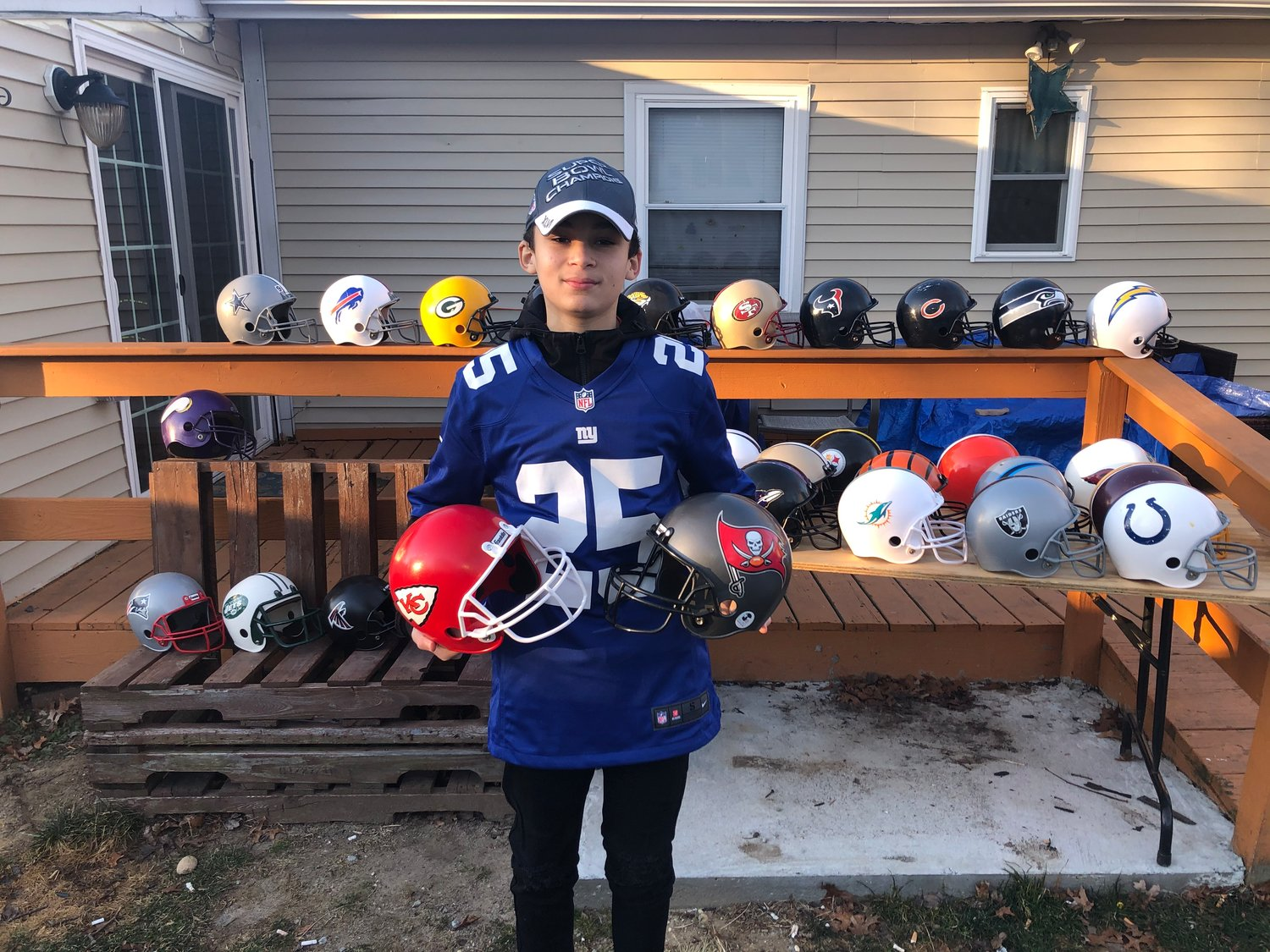 Donovan with his helmet collection holding this year's Super Bowl teams, the Buccaneers and the Chiefs.