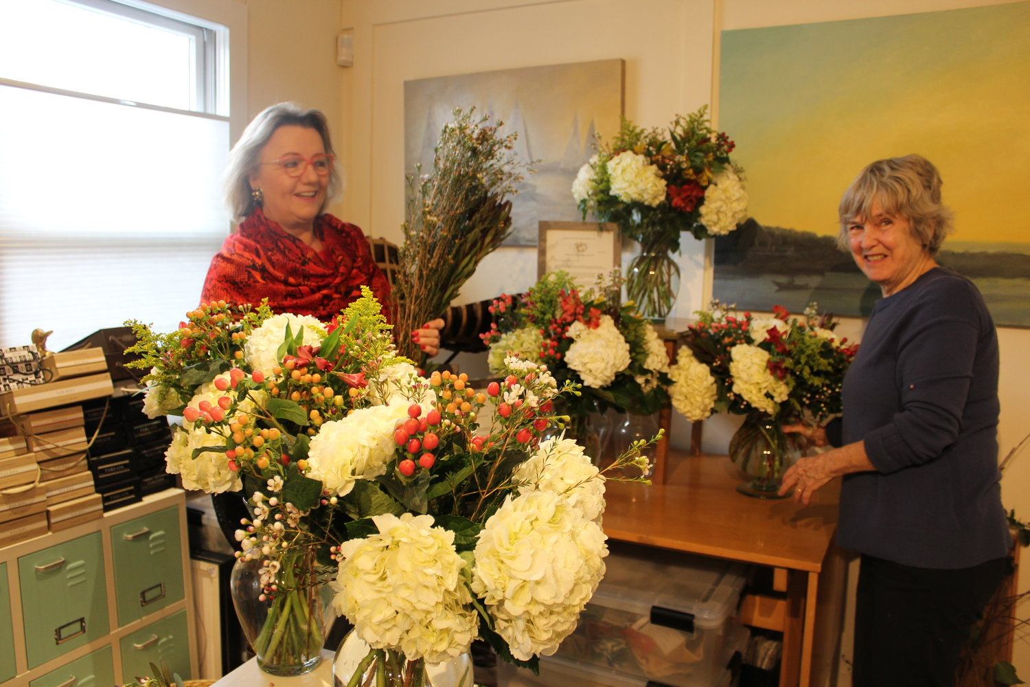 South Country Education Foundation board member and business owner Pamela Lerner shares a laugh with Bellport Garden Club civic chair Jane Tierney as they arrange flowers for teachers, a SCEF-sponsored event.