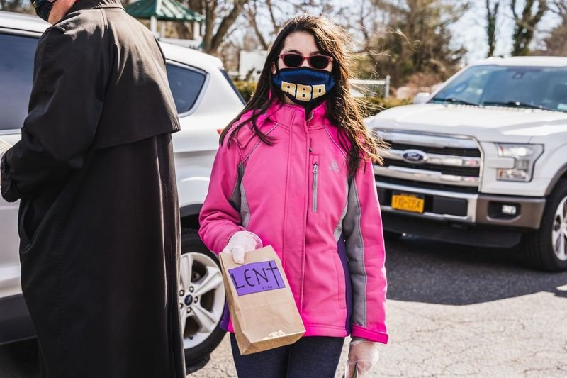 "Stina Czeisel, age 12, daughter of pastor Dave Czeisel, cheerfully handed out ""Lent Bags,"" which included a sealed container of ashes and miniaturized prayer stations. Each participant was guided in prayer and blessings for the Lenten season."