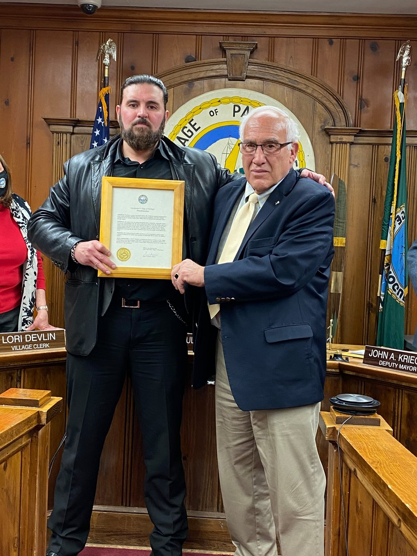 Patchogue Village Mayor Paul Pontieri honors former United States Marine Guillermo Sandoval with a Proclamation during a Village meeting on Monday.