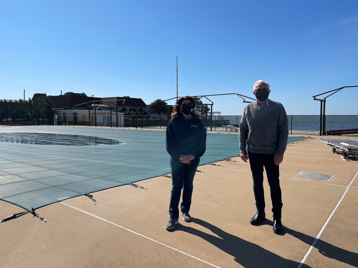 Parks director Maria Giustizia and trustee Joseph Keyes pose at the pool in anticipation of its reopening this summer.