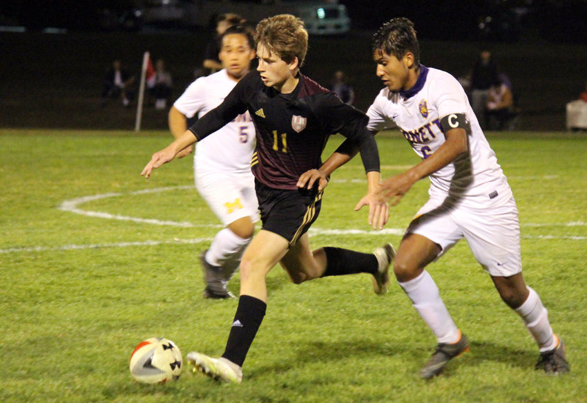 One of several freshman starters, Logan-Rogersville's Stewart McDonald possesses with his back to the defender in the first half of Thursday's district championship game in Aurora.