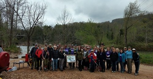 "A large group of volunteers stands together at the Ponca Access of the Buffalo River during a spring river cleanup. In the center of the group is a sign that says ""BNRP Volunteers at Work."" (BNRP)"