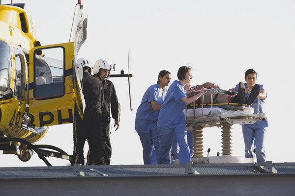 Medical personnel rushing patient from helicopter.