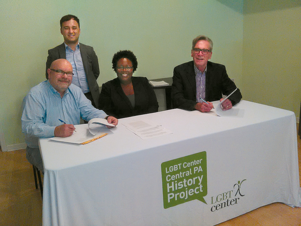 From left: Barry Loveland, chair, LGBT Center of Central PA History Project; standing, Louie Marven, executive director, LGBT Center of Central PA; Shaashawn Dial-Snowden, board chair, LGBT Center of Central PA, and Philadelphia historian and writer William Burton, signing a book contract from Pennsylvania State University Press June 8. Burton and Loveland will co-author a book on the history of the south central region's LGBT community. The book chronicles the evolution in the region's community from the 1940's through present day, from the creation of the first gay and mixed bars to the appearance of the early gay pioneer activists, to the creation of the first gay organizations and ending with a well-developed community infrastructure.