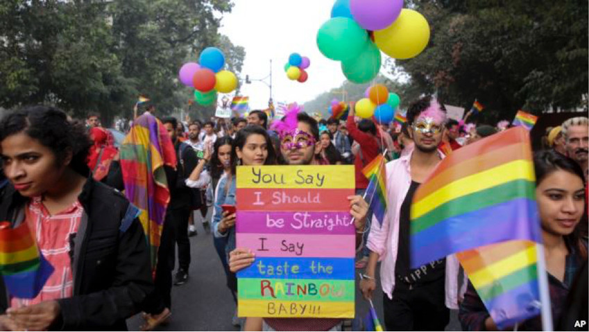 Gay rights activists and their supporters hold colorful balloons and placards as they participate in a gay pride parade in New Delhi, India, on November 12, 2017.