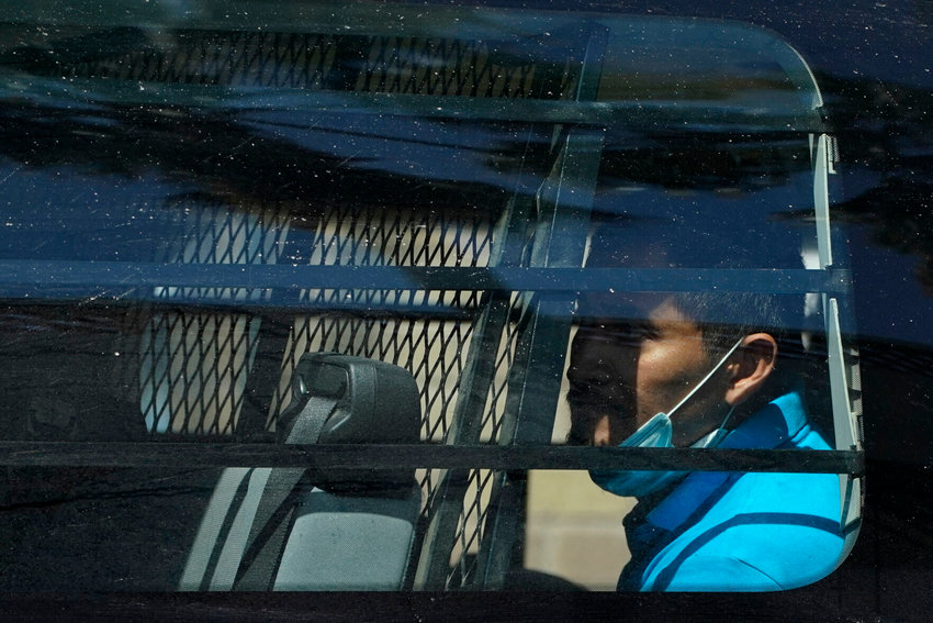A migrant is seen inside of a van near a respite center after being released from U.S. Customs and Border Protection custody, Friday, March 19, 2021, in McAllen, Texas. A surge of migrants on the Southwest border has the Biden administration on the defensive. The head of Homeland Security acknowledged the severity of the problem Tuesday but insisted it's under control and said he won't revive a Trump-era practice of immediately expelling teens and children.