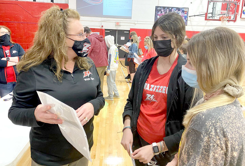SCIENCE TEACHER Natalie Brazeal, left, tells eighth grade students Isabelle Snodgras, center, and Kalgan Barker some of the things they can expect as freshman students during an open enrollment night held at West Plains High School this month.