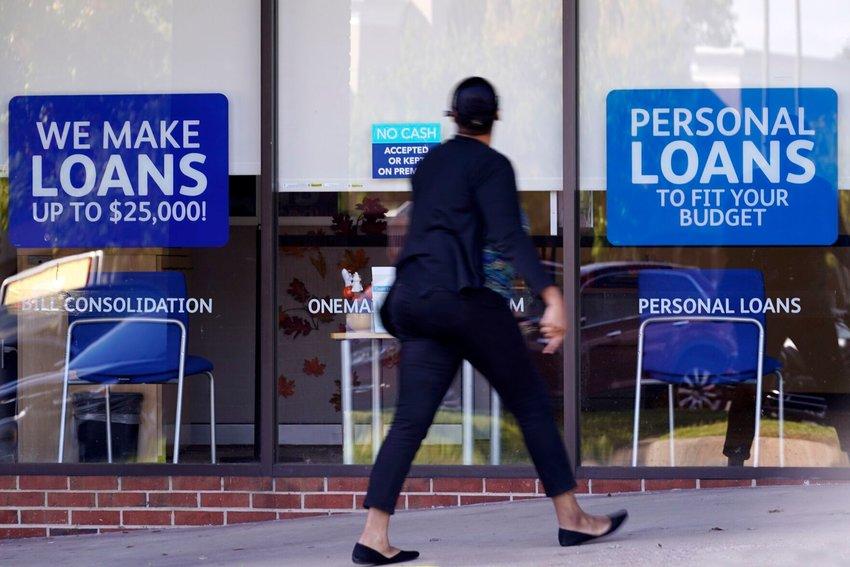 A woman walks past a personal finance loan office Thursday, Oct. 1, 2020, in Franklin, Tenn.