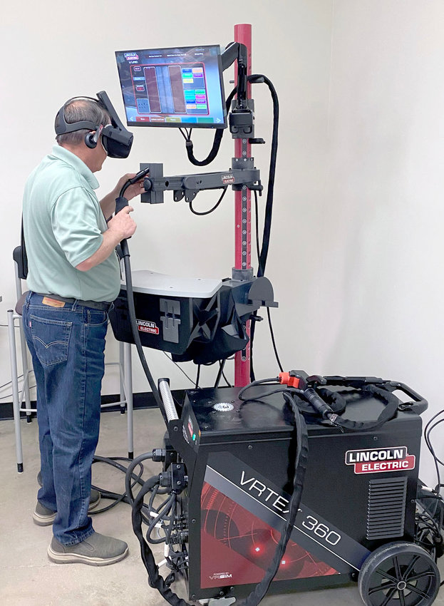ROY CROUCH, education and employment outreach specialist at Missouri State University-West Plains, demonstrates the VRTEX 360 virtual reality welding training simulator. This new piece of equipment will give students the ability to practice various welding methods in a realistic setting as displayed in the VR goggles he is wearing. Students can simulate specific welds, techniques and processes while the system tracks their progress, helping them learn when to adjust their techniques and be more prepared when they use actual welders.