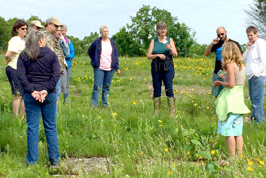 Sasha Daucus, fourth from right, guides a tour group around Buck Hollow at Jacks Fork in Texas County.