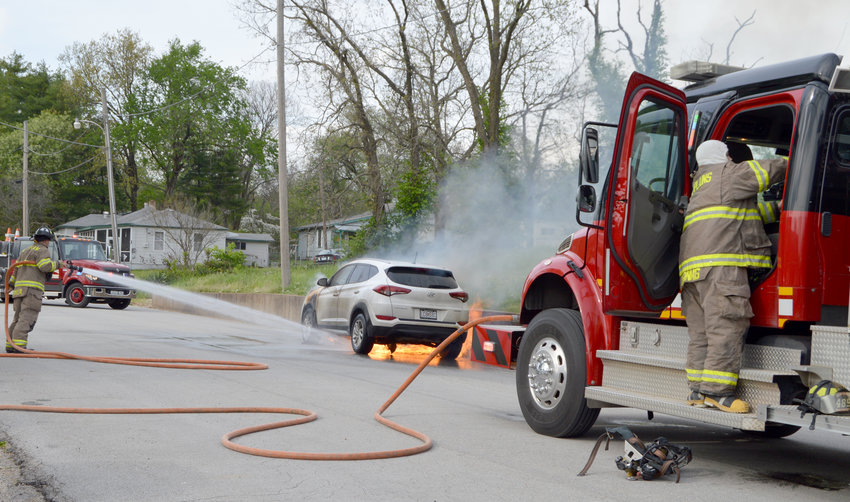 """""""THINGS COULD BE WORSE,"""" was the attitude of West Plains resident Thomas Kazmir, whose day took a turn when he heard a popping sound coming from under the hood of his vehicle around 5 p.m. Thursday as he drove north on Lincoln Avenue. Kazmir said he was trying to park his 2017 Hyundai Tucson farther away from houses, but the engine compartment caught fire before he could. Firefighters and police officers were dispatched about 5:13, after being warned there was live ammo in the passenger compartment of the SUV, and the fire was under control at about 5:40. Kazmir was uninjured during the incident and tried to remain upbeat, although he commented he pretty much lived out of his car because he works a lot and most of his possessions, including his clothing, were in it.West Plains Fire Department Lt. Wayne Cormier, left, turns a hose on the flames, as firefighter Sage McGinnis grabs gear from the truck."""