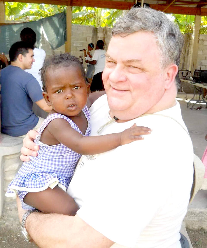 """Bob Andrews, a physician assistant and longtime Good Samaritan Care Clinic, was known for his kindness to children and adults alike, fellow volunteers recall. On medical mission trips to Haiti, where this photo was taken, he was described """"a big hit with children."""""""