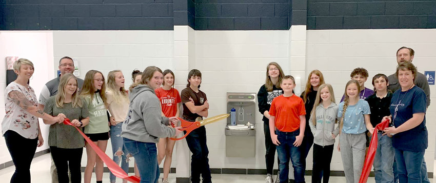 """LIBERTY MIDDLE SCHOOL Student Council members in Mtn. View held several fundraisers over the course of this school year to raise over $1,000 to purchase water fountain attachments for filling bottles. They organized a Santa's Workshop, a """"Crush"""" fundraiser for Valentine's Day, """"hat days,"""" and sold items and volunteered at a Mtn. View Youth Center dance to raise $1,040.60. The funds went to two attachments, installed on water fountains in the cafeteria and the eighth grade hall, which make filling water bottles a faster process. """"Students will no longer have to wait in such lengthy lines or ask teachers to leave to fill up their bottles as often to avoid being late,"""" said Mtn. View Chamber of Commerce Director Gretchen Creighton, adding the chamber chose to celebrate the youths' efforts with a ribbon cutting ceremony """"to help make the kids feel special."""" From left: Creighton, Principal Ryan Chowning, STUCO Sponsor Shelly Renegar, Kelbie Smith, Bently Lawson, Jade Acklin, STUCO President Ashlynn Henry cutting the ribbon, Liz Fisher, Reece Walton, Taylor Manley, Max Smith, Lillie McAdams, Madelyn Smith, Emma Faulkner, Landon Hines, DeWayne McClellan, chamber board member Matt Willbanks and STUCO Sponsor Mitzie Pennycuick."""