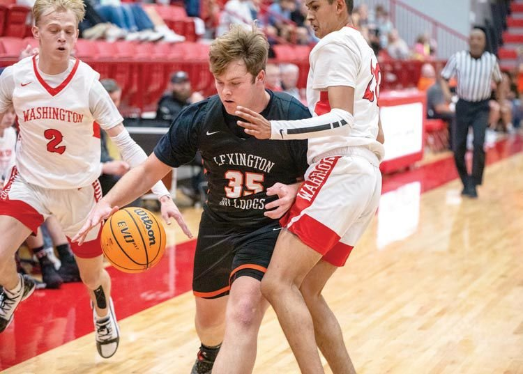 Colton Penner dribbles around the Warrior defense during Lexington's game at Washington. The Bulldogs fell 49-42.