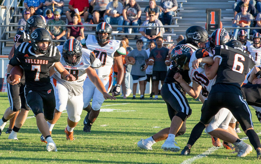 Wayne senior Ethan Mullins (7) races right while Jairo Hernandez (6) walls off the Apache defense Friday night. Mullins ran for 200 yards and scored three touchdowns in Wayne's season-opening 37-6 win over the Warriors.