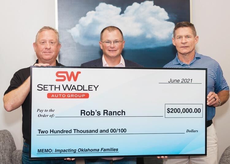 Seth Wadley, center, presents Rob's Ranch director Doug Hayes, left, and Kelly Rose, board of directors of Rob's Ranch, with a check for $200,000 to help build a new residential dormitory at the facility in Purcell.