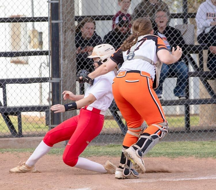 Lexington senior Jaci Idlett tags out a Davis base runner at home during the Bulldogs' 15-14 win over the Wolves.