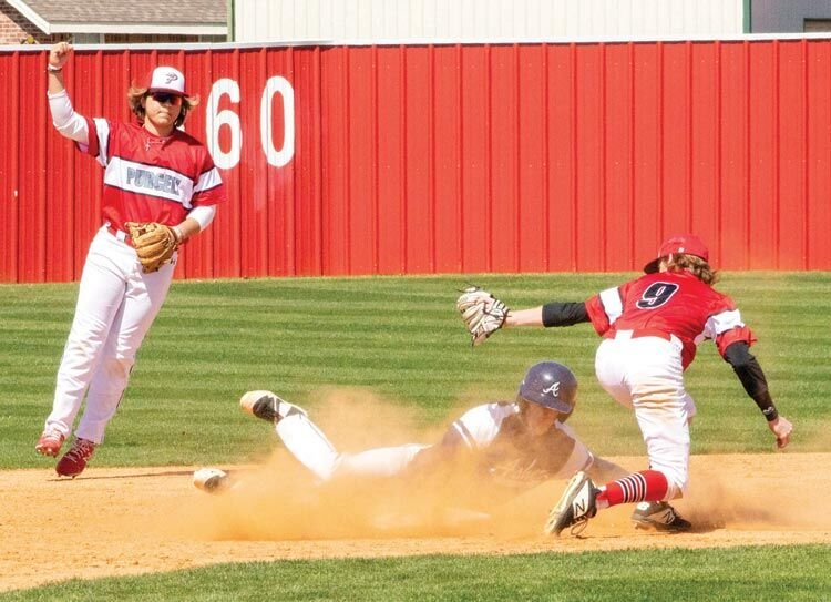 Purcell junior Hayden Harp makes the call while senior Cade Smith slaps a tag on an Asher base runner. The Dragons were defeated 14-6 by the Indians.