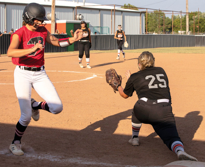 Lexington senior Ryli Harmon catches a ball from Kiely Givens for an out at first base against Purcell. The Bulldogs were defeated 10-2 by the Dragons.