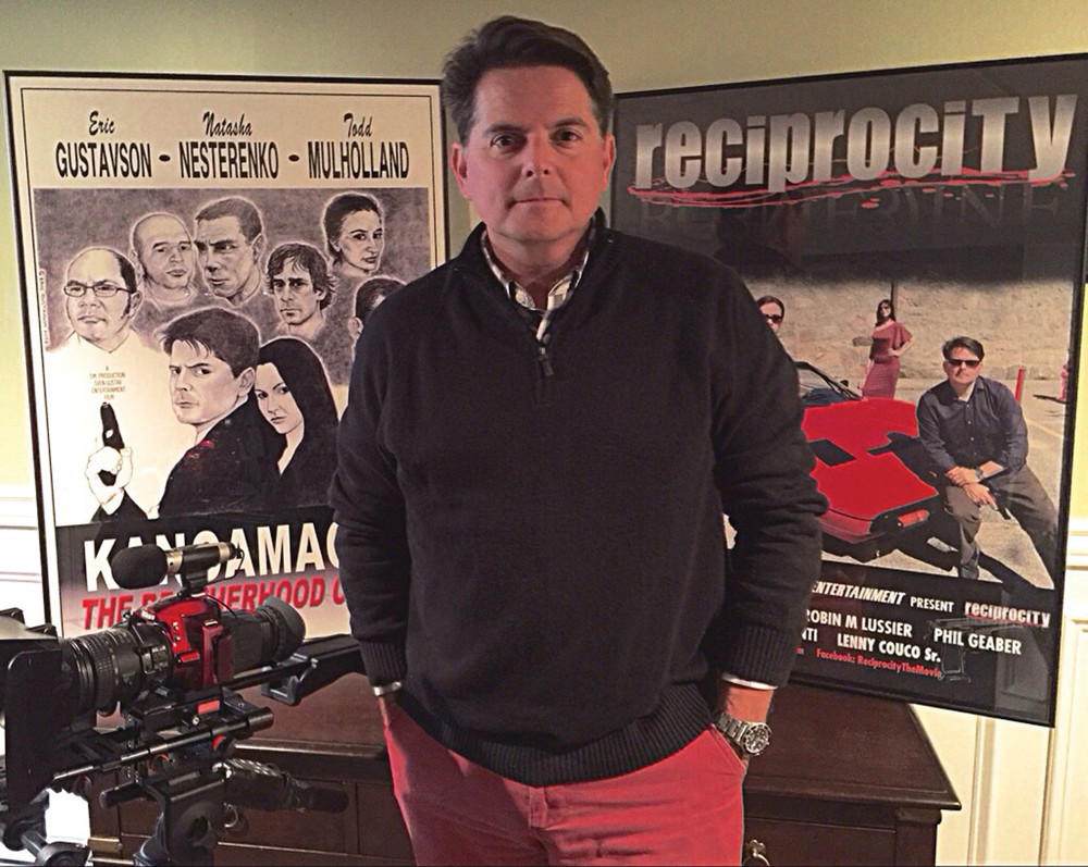 GRASSROOTS FILMMAKER: Todd Mulholland has been following his passion, making movies, for 20 years. Seen here with his camera, and flanked by the movie posters from his last two movies, Mulholland and his family are looking ahead to the filming of his next movie, a suspense thriller.