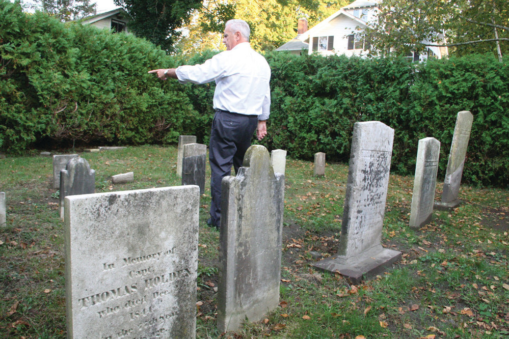RESTORED:  Councilman Ladouceur admires the restored cemetery.