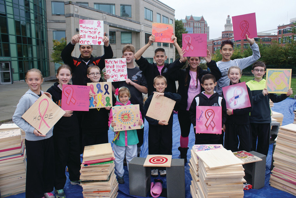 BREAKING BOARDS: Mastery Martial Arts held a live demonstration during the Gloria Gemma Breast Cancer Resource Foundation's Flames of Hope. People bought and decorated a board and watched as the messages on them were broken as a tribute to loved ones. There were 5,000 boards in total. Pictured is Mastery Martial Arts of Cranston program director Michael Rossi Jr. with some of his students.