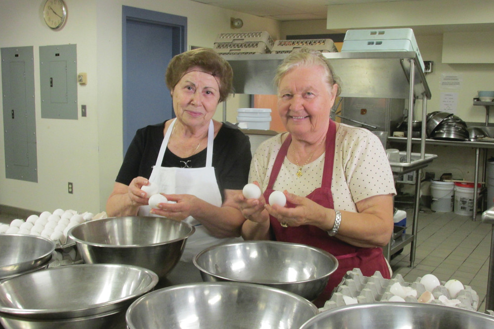 CLASSIC CAKE: Liza Petrou and Sylvia Gionis are cracking eggs to help make karydopita, a Greek walnut cake glazed with Greek honey syrup, that will be on sale this weekend at the Cranston Greek Festival.