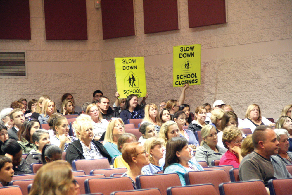 """SLOW DOWN: Hearing attendees hold signs asking the committee to """"slow down school closings."""""""