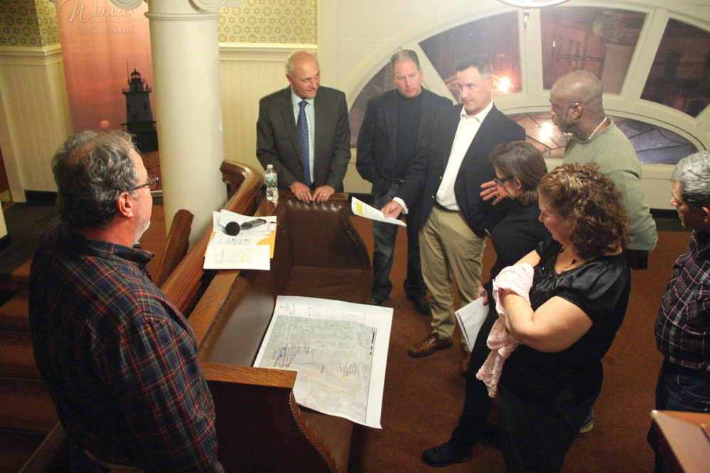 HALLWAY REVIEW: Ralph Palumbo (at left rear) of Southern Sky Renewables meets with neighbors to the proposed solar park on West Shore Road prior to Monday's council meeting.