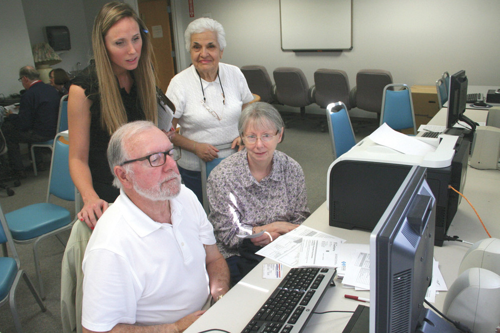 CONSIDERING THE OPTIONS: With Annemarie Walker seated beside him, Senior Health Insurance Program (SHIP) volunteer Eric Robinson reviews Medicare plans at the Pilgrim Senior Center. Looking on are Kathleen Bennett, who manages the center program, and volunteer Sylvia Dulgarian.