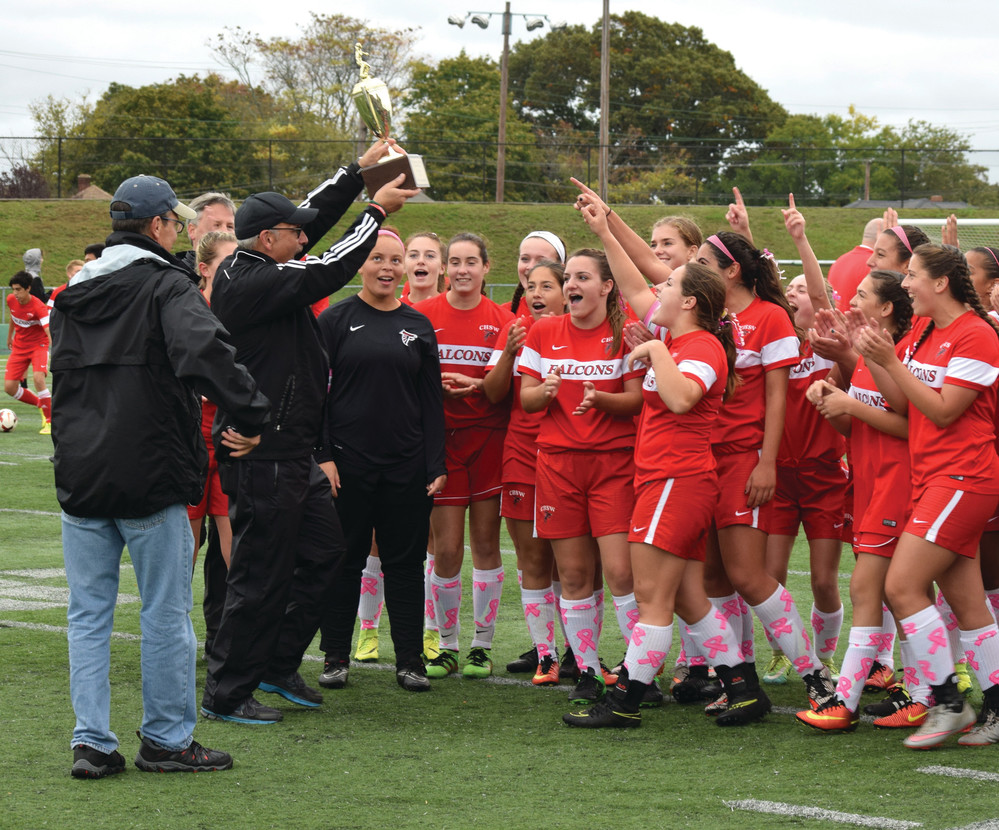 WESTWARD BOUND: The West girls' team celebrates as Head Coach Jeremy Sherer raises the trophy.