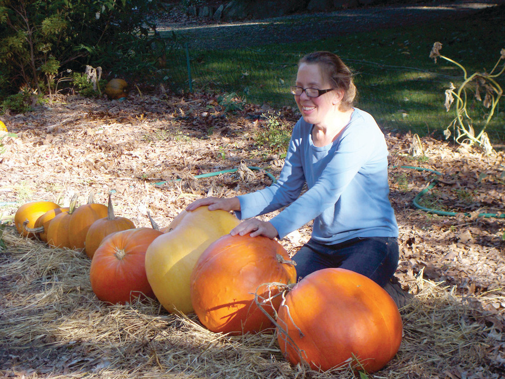 PLENTY OF PUMPKINS: Rhonda Shumaker, co-owner of the Rocky Point Farm, prepares some of the many pumpkins that were seen during the Pumpkin Walk which drew thousands of attendees.