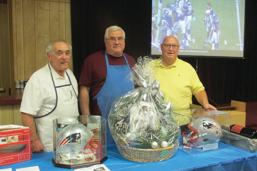 PASTOR'S PALS: Joe Grasso and Joseph Quartino were among the many proud parishioners at OLG who helped Rev. Peter J. Gower host a Super Bowl-like tailgate party Sunday. Above, they're standing behind the raffle table that included two Rob Gronkowski autographed helmets.