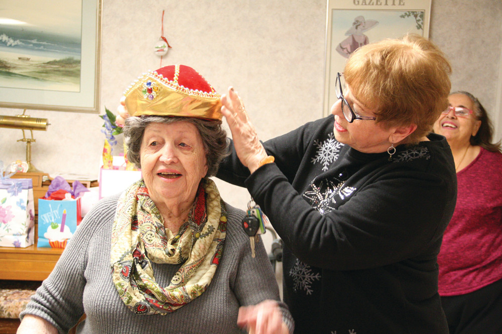 CROWNED: Nancy DeShaies fits a crown on Frances Amico as Greenwood Terrace tenants gathered Saturday to celebrate Frances' 102nd birthday. Nancy and Roseanne Andrews, looking on from back, planned the surprise party.
