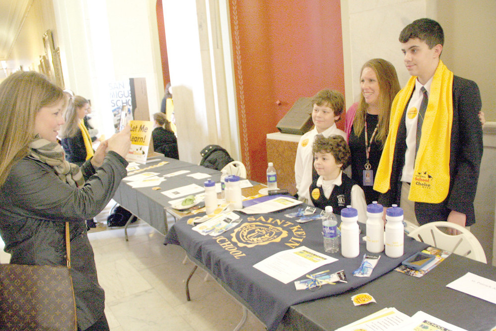 JOINING THE CAUSE: Jenn Monti gets a photo of her sons Jude and Rowan and Becki Manzo and Ryan McGrath at the St. Kevin School table.