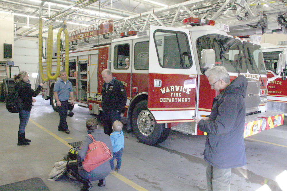 CENTER OF ATTENTION: Ladder 4 was popular during the open house with children and their parents getting to sit behind the wheel or look out the window, as Abby Morse does here.