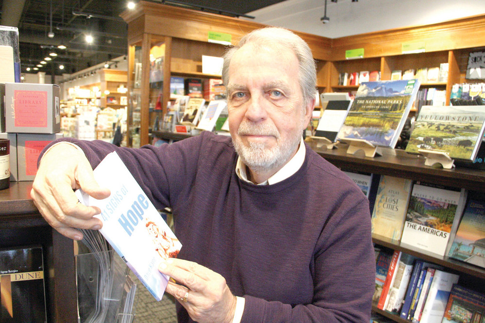 THERE'S HOPE FROM TRAGEDY: Dave Kane holds a copy of his book 41 Signs of Hope that is being sold at Barrington Books and Barnes and Noble with proceeds going to the Station Fire Memorial under construction at the site of The Station Nightclub, where 100 died on Feb. 20, 2003.
