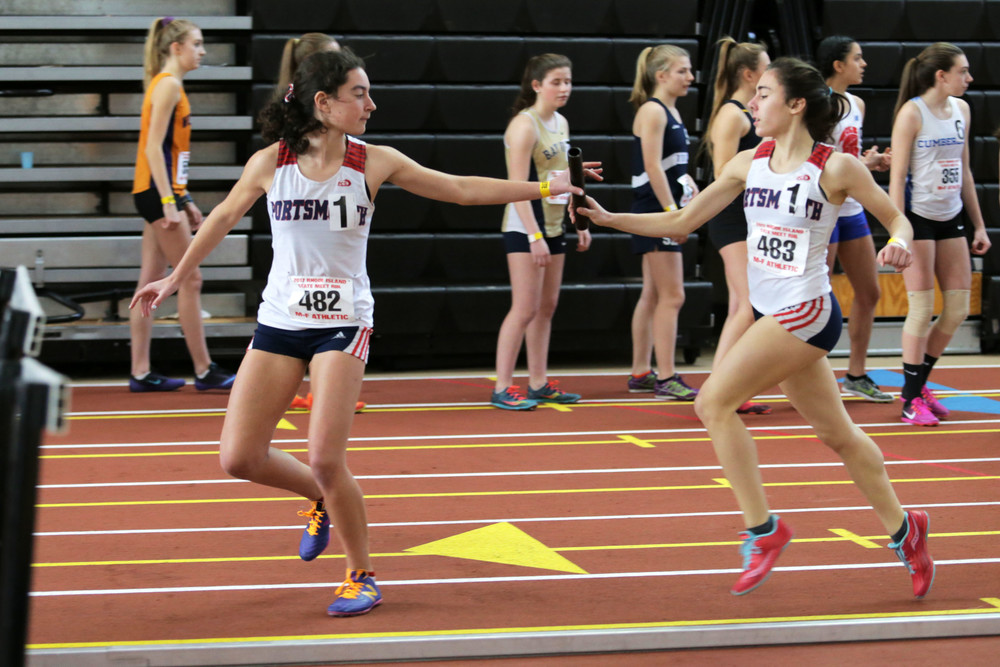 Sophomore Elizabeth Sullivan is handed the baton by teammate Sofia White during their victory in the 2x800-meter relay race.